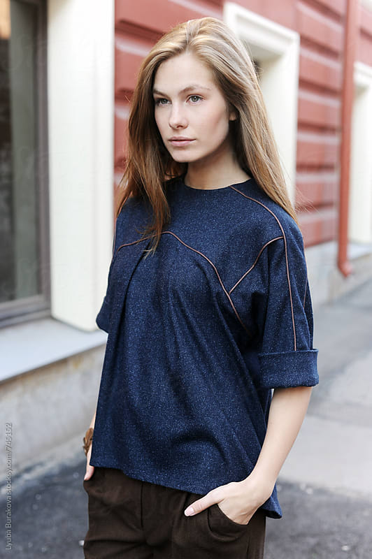 Beautiful young woman standing on the street by Lyuba Burakova for Stocksy United