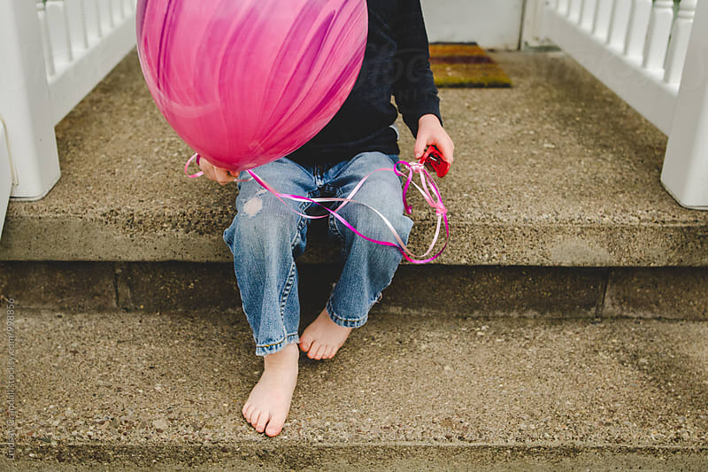 Child holding a balloon on porch steps by Lindsay Crandall for Stocksy United