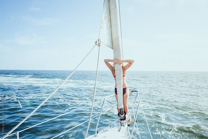 woman vacationer relaxes on the bow of a sailboat  by HOWL for Stocksy United