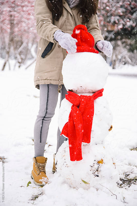 Young woman standing behind a snowman by Danil Nevsky for Stocksy United