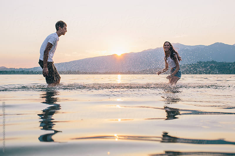 Couple splashing water by michela ravasio for Stocksy United