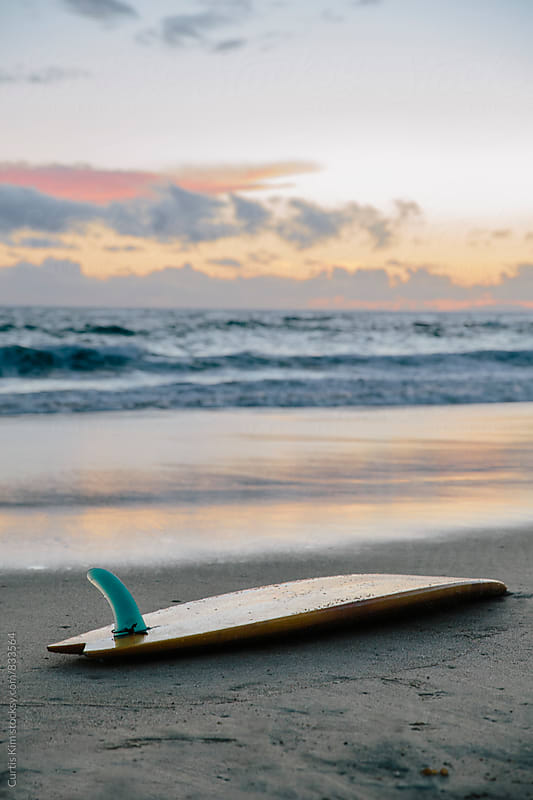 Surfboard washed ashore from the sea by Curtis Kim for Stocksy United