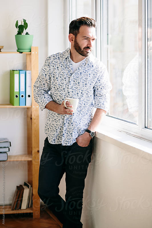 Bearded man drinking coffee at the office by Aleksandar Novoselski for Stocksy United