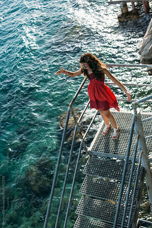Girl throwing a little stone to the sea from a staircase by Beatrix Boros for Stocksy United