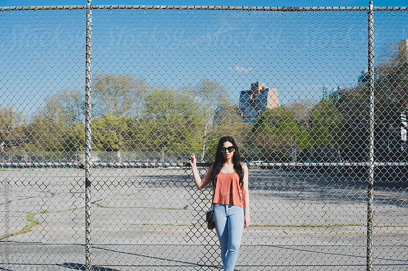 Young woman in sunglasses standing against fence by Lauren Naefe for Stocksy United