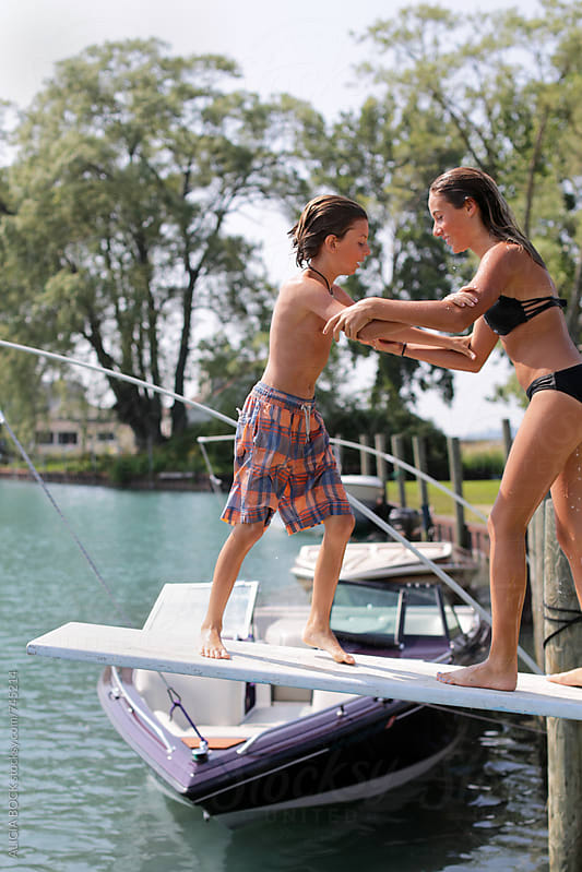 Siblings Playing On A Diving Board On The Edge Of A Lake On A Summer Day by ALICIA BOCK for Stocksy United
