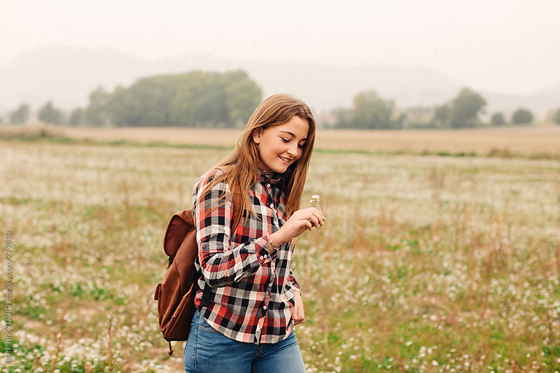 A 14 years old girl walking in a flowery field on a foggy day. by BONNINSTUDIO for Stocksy United