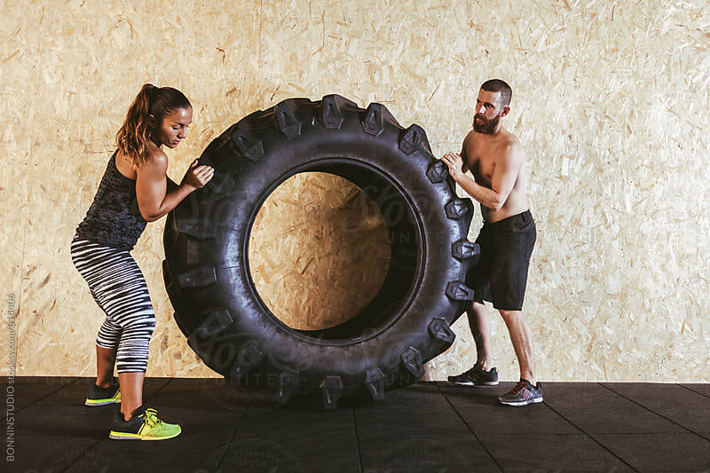 Couple working out with a heavy tire in a gym box. by BONNINSTUDIO for Stocksy United