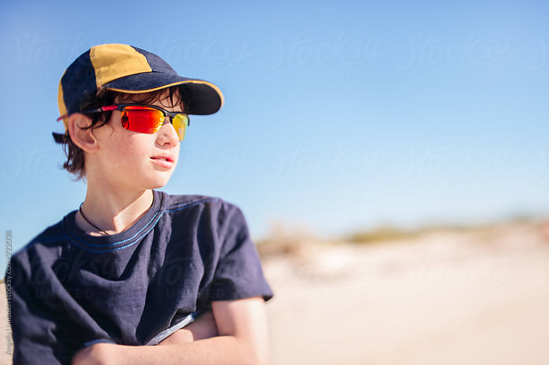 Boy with cap and sunglasses at the beach on a sunny afternoon by Angela Lumsden for Stocksy United