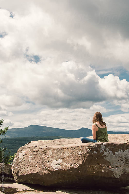 girl sitting on rock on mountain looking at view  by Deirdre Malfatto for Stocksy United