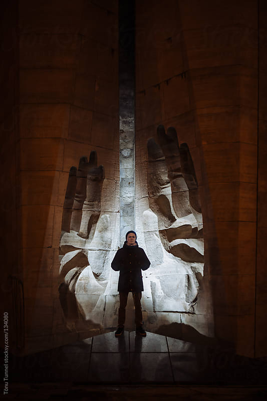 A boy standing in front of a soviet monument by Tõnu Tunnel for Stocksy United