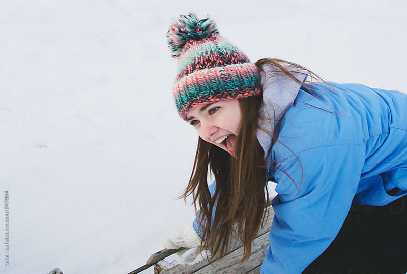 young woman laughing while preparing to sled by Tana Teel for Stocksy United