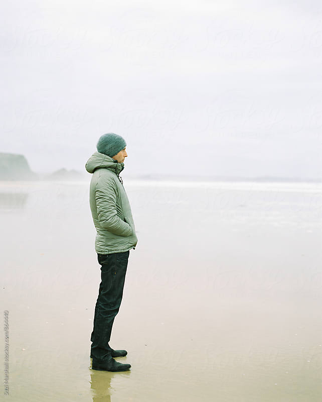 Man standing on a beach on a foggy winter day looking out to sea by Suzi Marshall for Stocksy United