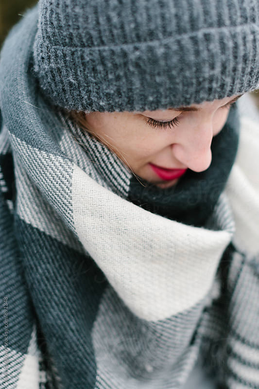 Young woman wrapped in gray winter clothes by Amir Kaljikovic for Stocksy United