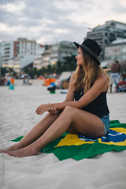 Rio de Janeiro. Brazil. Woman relaxing on the beach at sunset by Mauro Grigollo for Stocksy United