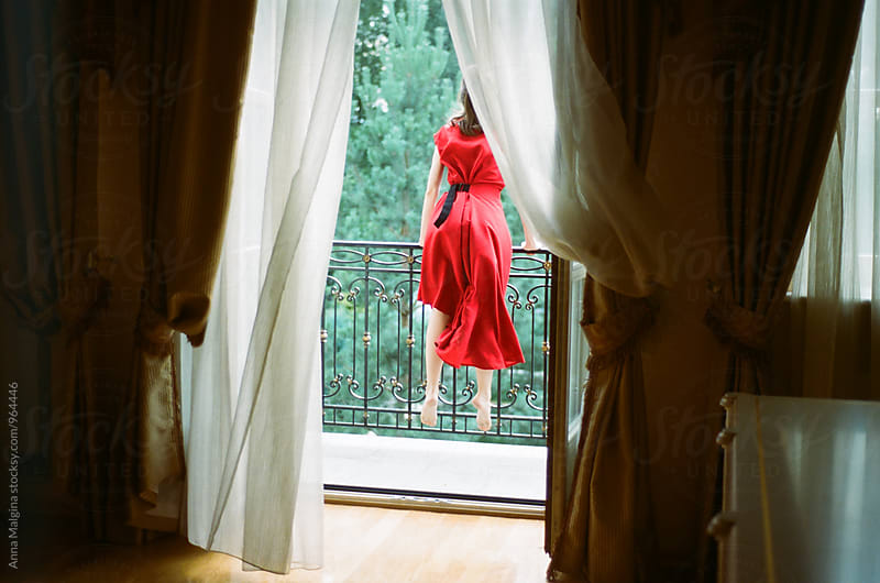 A film portrait of young beautiful woman with red dress standing on the balcony by Anna Malgina for Stocksy United