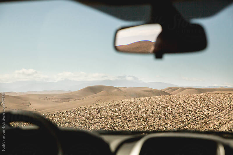 Driving though the stone desert in Morroco by Sophia van den Hoek for Stocksy United