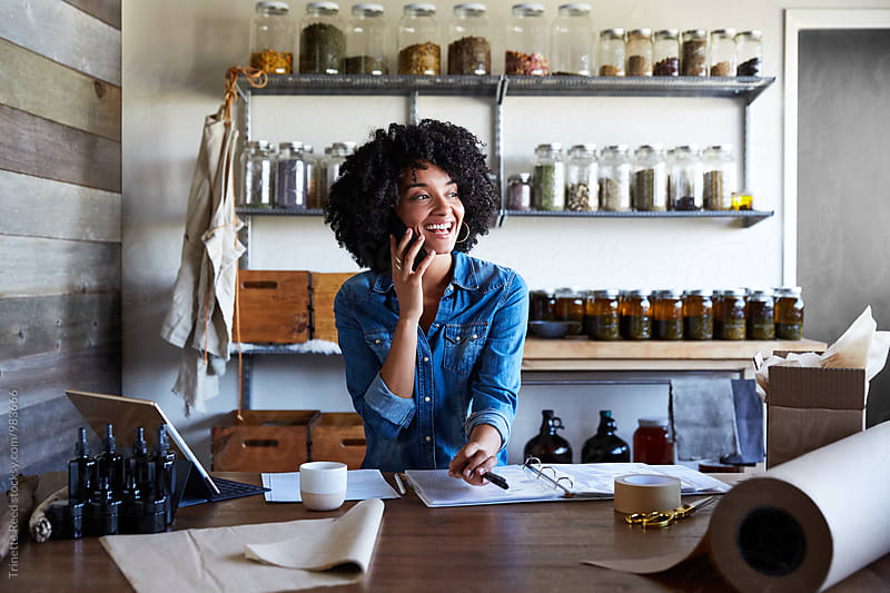 Millennial African American Woman businesswoman on the phone in her skincare studio by Trinette Reed for Stocksy United