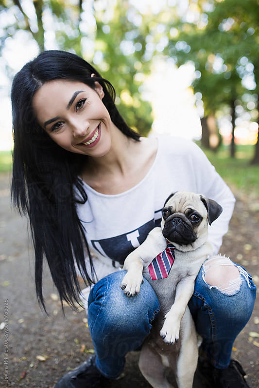 Young woman and her pet pug dog in a park by Jovana Rikalo for Stocksy United