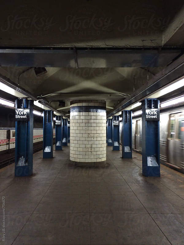 A subway train arrives at an underground station. by Riley J.B. for Stocksy United
