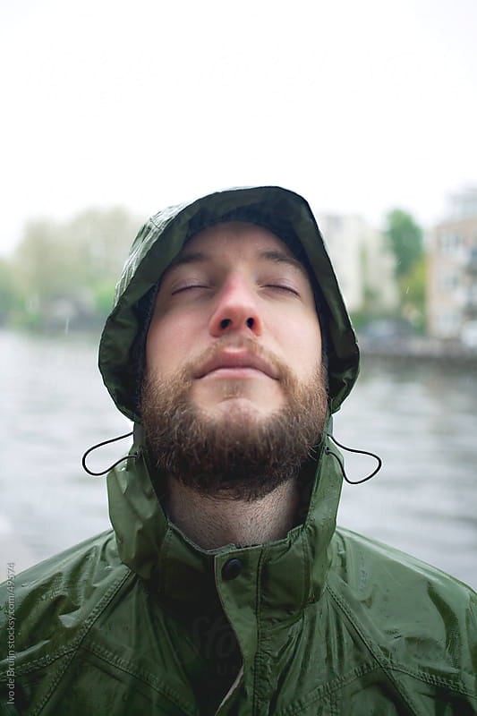 A young man with a beard standing in the rain with his eyes closed by Ivo de Bruijn for Stocksy United