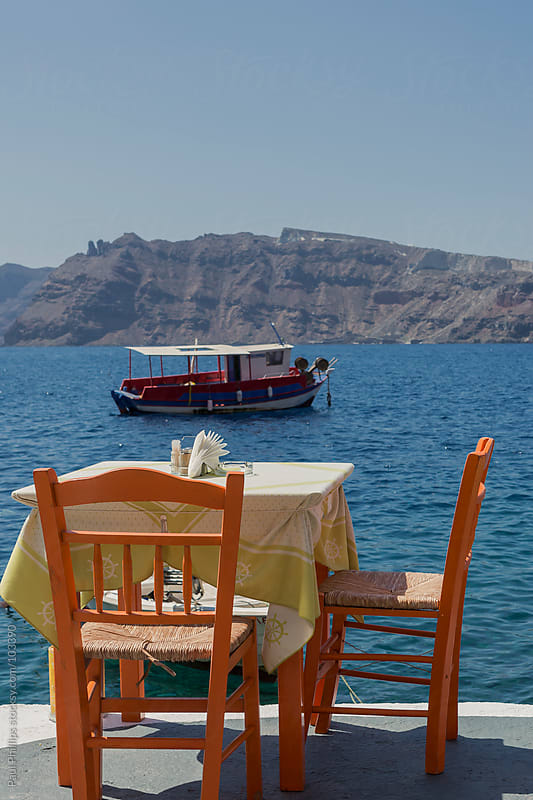 Table and chairs by the bay in Oia, Santorini, Greece by Paul Phillips for Stocksy United