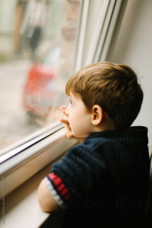 Cute boy looking through the window, vertical by Marija Kovac for Stocksy United