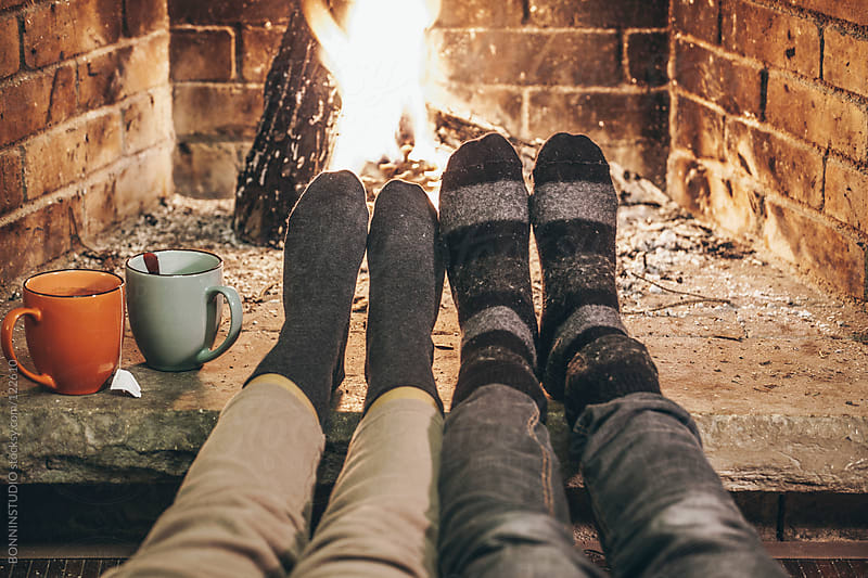 Couple in wool socks warming by cozy fire. by BONNINSTUDIO for Stocksy United