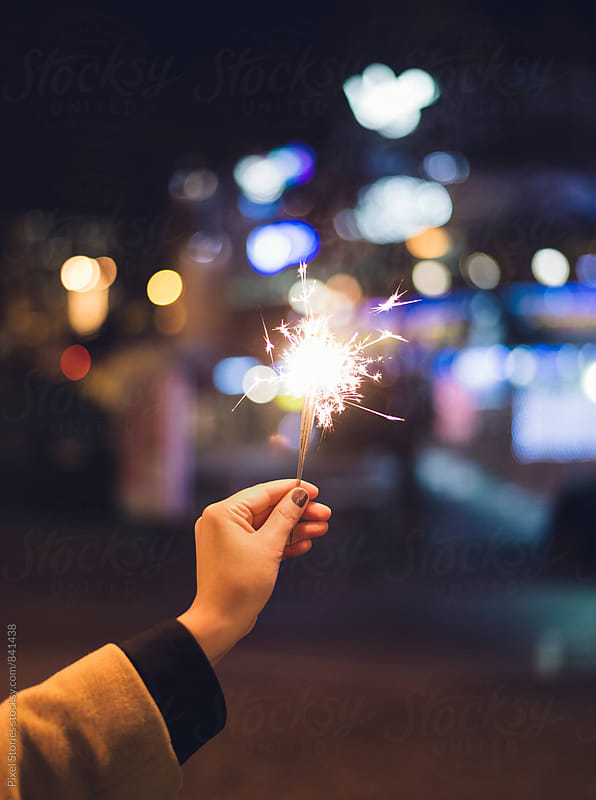 Young woman holding sparkler by Pixel Stories for Stocksy United