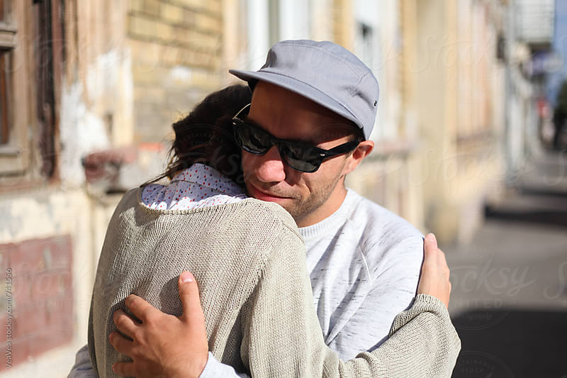 Young man and woman hugging in the street  by VeaVea for Stocksy United