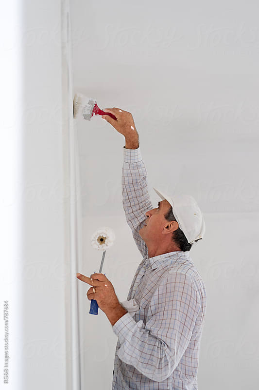 Senior man carefully painting the home walls white by RG&B Images for Stocksy United