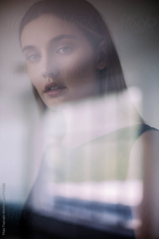 Beautiful woman looking through a window by Maja Topcagic for Stocksy United