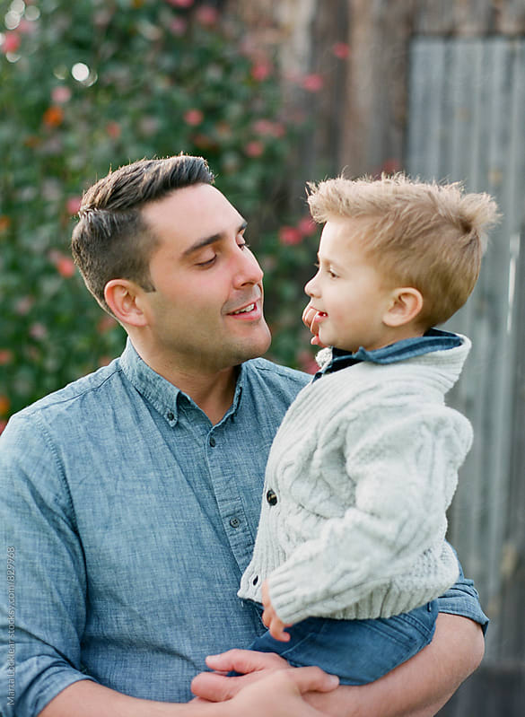 Dad holding his toddler son by Marta Locklear for Stocksy United