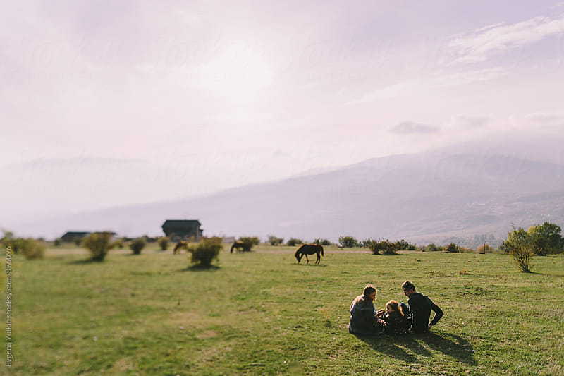 Family sitting on the hillside by Evgenij Yulkin for Stocksy United