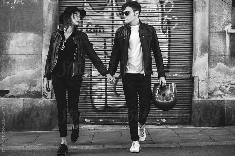 Biker couple holding hands walking on the street. by BONNINSTUDIO for Stocksy United