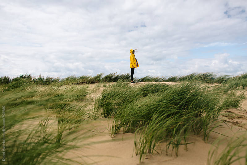 Woman standing on dunes in the wind wearing a yellow raincoat by Denni Van Huis for Stocksy United