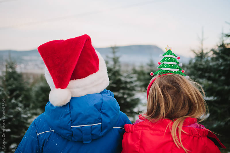 Christmas tree hunt at the tree farm with festive hats by Rebecca Zeller for Stocksy United