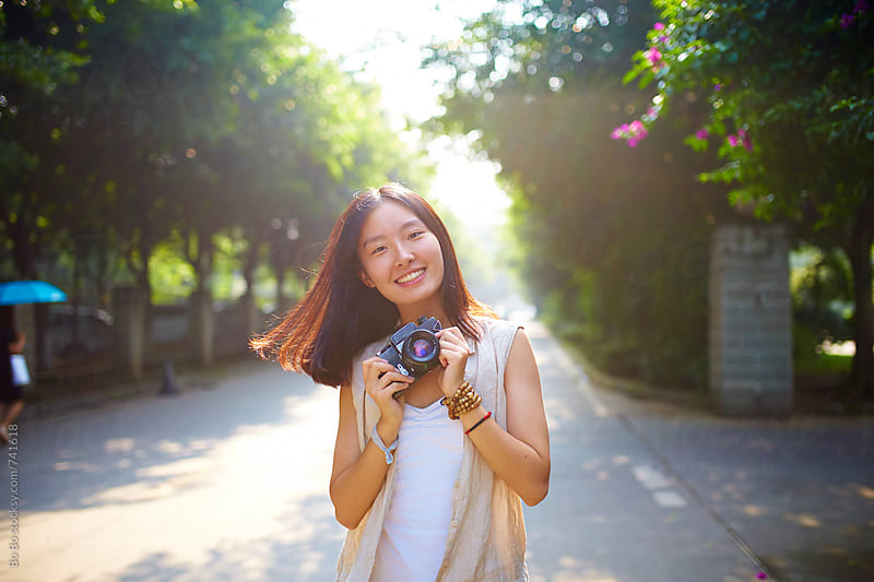 pretty young asian woman smile at camera with camera in hand by Bo Bo for Stocksy United