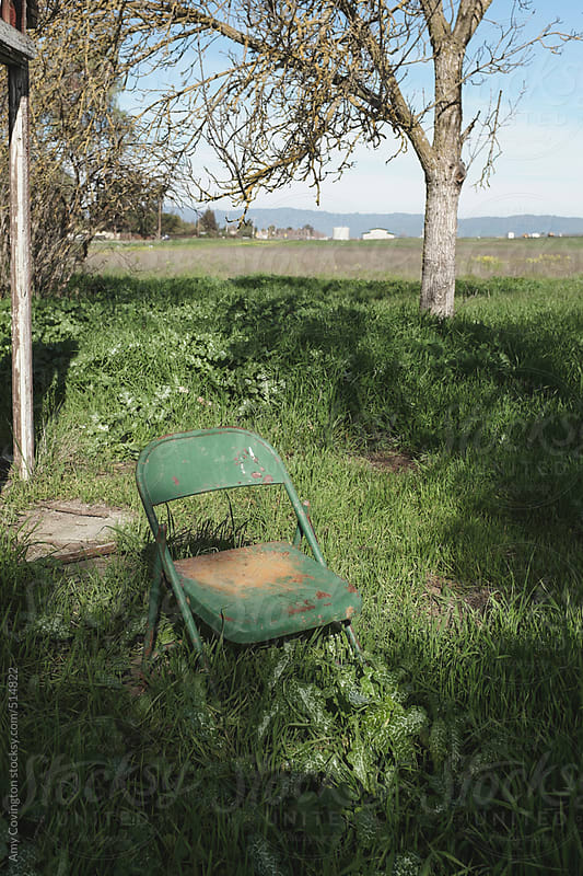 Green folding chair surrounded by grass by Amy Covington for Stocksy United