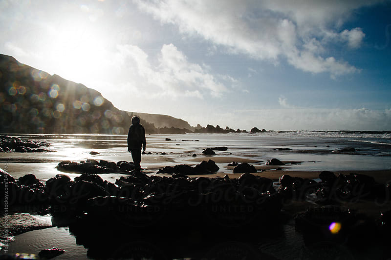 The silhouetted figure of a boy on a rocky beach by Helen Rushbrook for Stocksy United