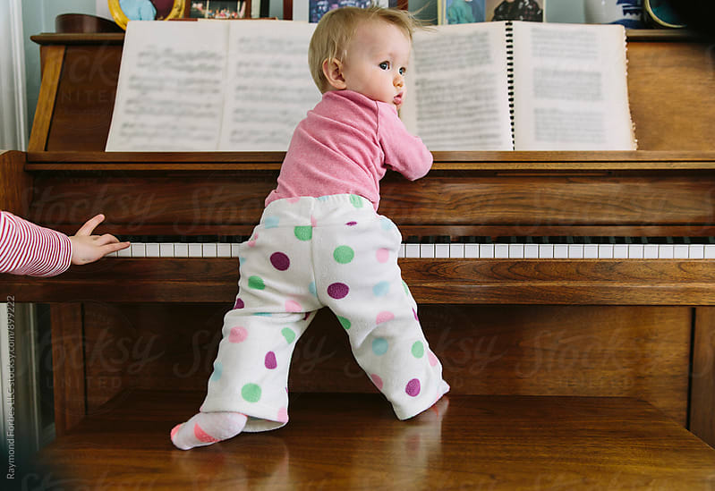 Toddler Playing at Piano with Brother by Raymond Forbes LLC for Stocksy United