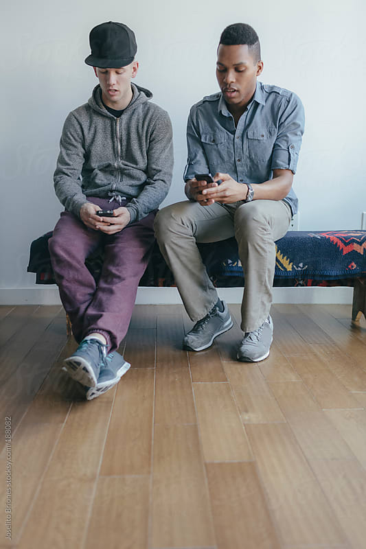 Young Men Friends Hanging Out Using Smart Phone by Joselito Briones for Stocksy United