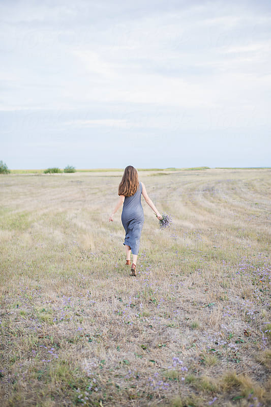 Young woman running in a field and holding flower bouquet by Jovana Rikalo for Stocksy United