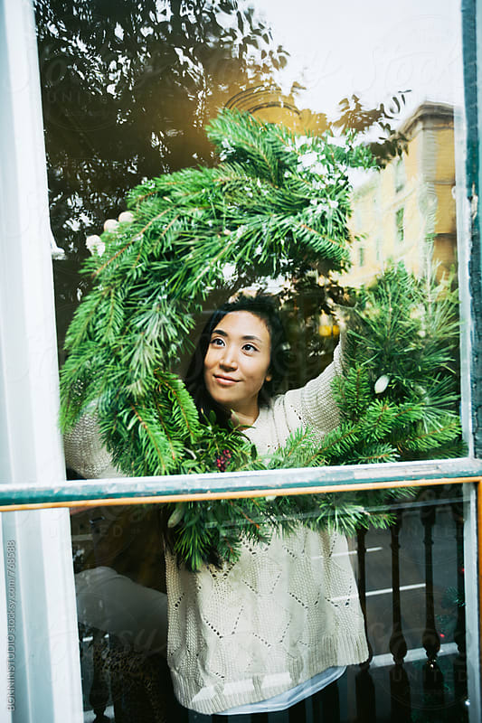 Young asian woman hanging a Christmas wreath on a window at home. by BONNINSTUDIO for Stocksy United