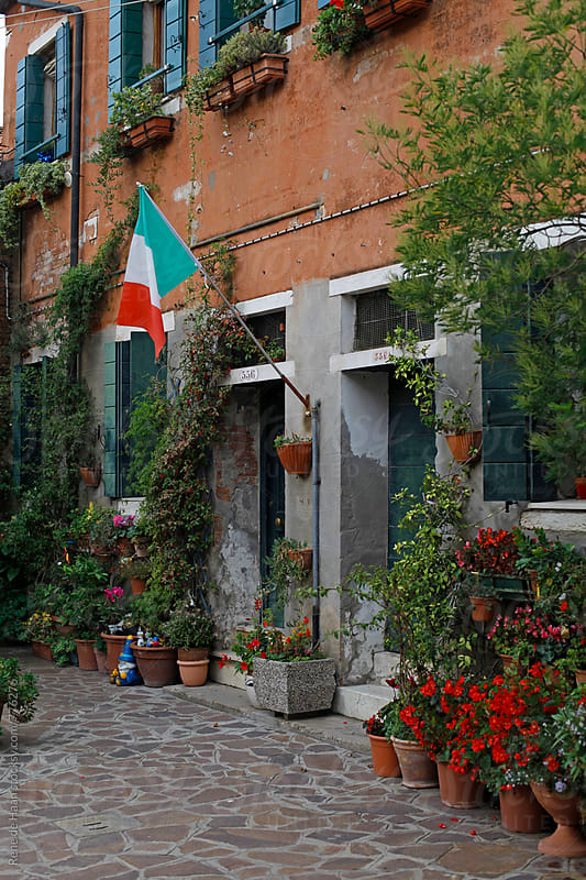 italian flag on house in Venice, Italy by Rene de Haan for Stocksy United