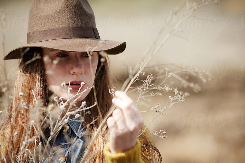 Woman touching plant in nature by Trinette Reed for Stocksy United