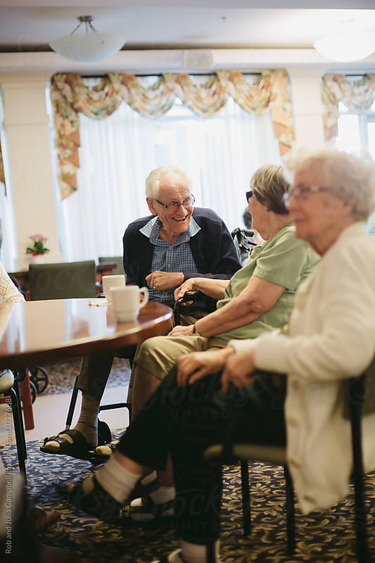 Group of senior folks hanging out around table by Rob and Julia Campbell for Stocksy United