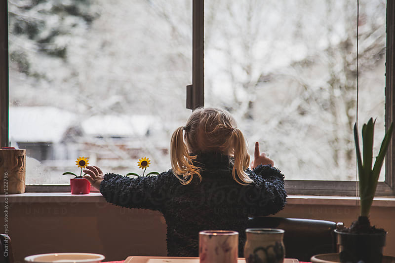 Little girl gazes out window at the snow. by Cherish Bryck for Stocksy United