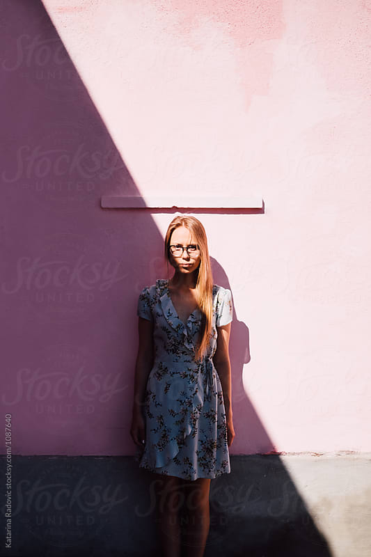 Portrait of A Young Woman in Front of the Pink Wall by Katarina Radovic for Stocksy United