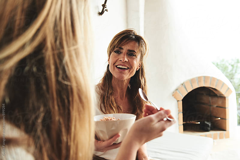 Adult woman chatting with another woman who holding plate by Guille Faingold for Stocksy United
